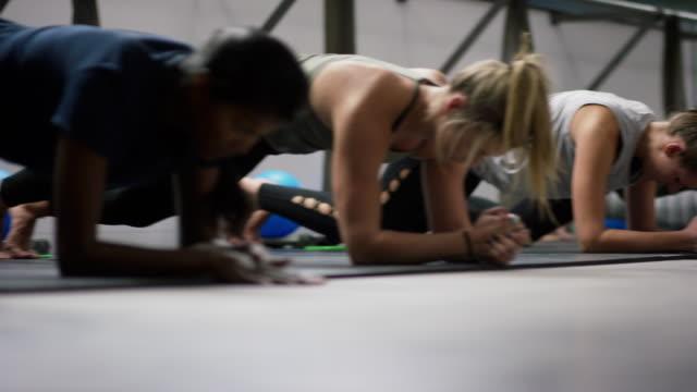 ett multietniskt grupp kvinnor i tjugoårsåldern hovra i planka position och sedan sträcka på golvet i en barre motion studio - balettstång bildbanksvideor och videomaterial från bakom kulisserna
