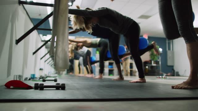 ett multietniskt grupp kvinnor i tjugoårsåldern utför benövningar på en balett barre i en motion studio - balettstång bildbanksvideor och videomaterial från bakom kulisserna