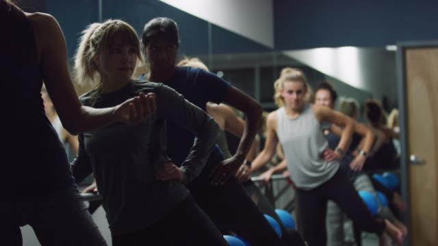 ett multietniskt grupp kvinnor i tjugoårsåldern utför benövningar med fitness bollar i en klass på en motion studio - balettstång bildbanksvideor och videomaterial från bakom kulisserna