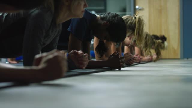 un gruppo multietnico di donne ventenni esegue flessioni e tavole in uno studio di esercizi - metodo pilates video stock e b–roll