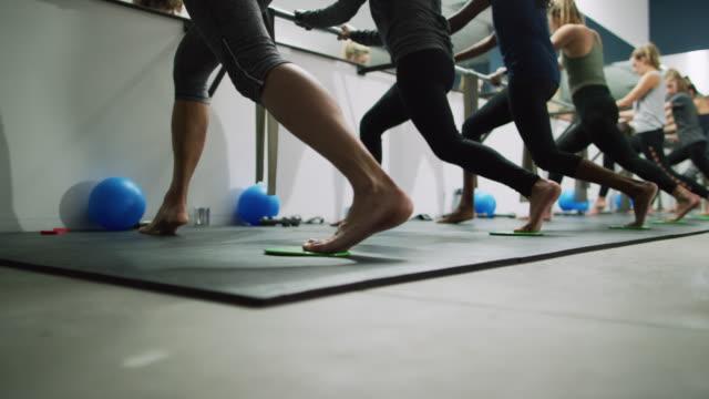 ett multietniskt grupp kvinnor i tjugoårsåldern puls i ett utfall position på en balett barre i en motion studio - balettstång bildbanksvideor och videomaterial från bakom kulisserna