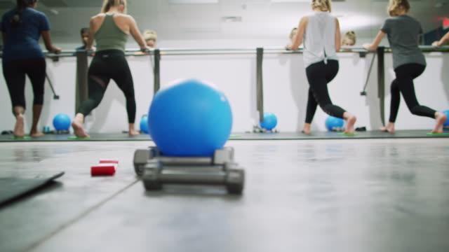 ett multietniskt grupp kvinnor i tjugoårsåldern puls i utfall position på en balett barre i bakgrunden på en motion studio med en fitness boll och hantlar i förgrunden - balettstång bildbanksvideor och videomaterial från bakom kulisserna