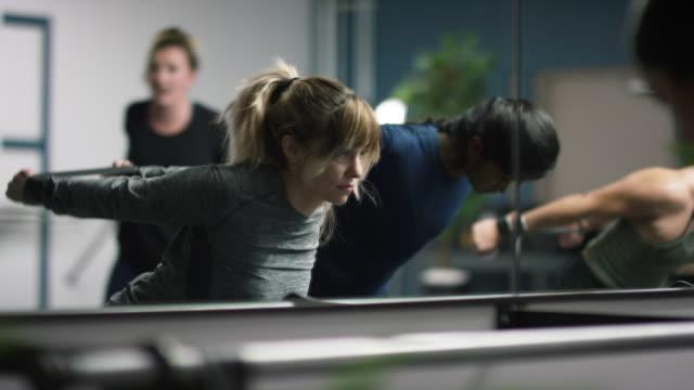 ett multietniskt grupp kvinnor i tjugoårsåldern puls med fitness band på deras armar bakom dem i en motion studio - balettstång bildbanksvideor och videomaterial från bakom kulisserna