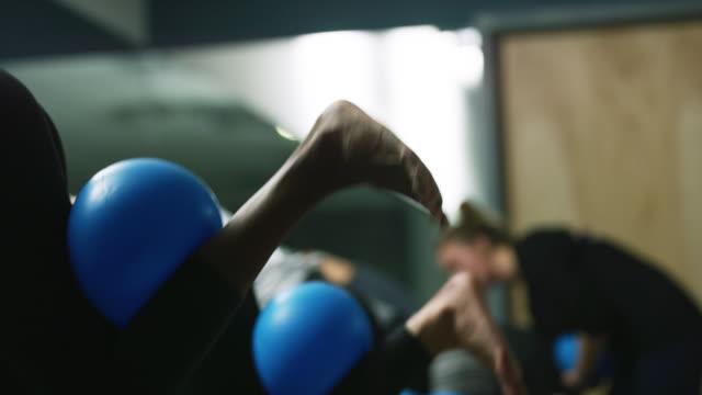un gruppo multietnico di donne esegue esercizi per le gambe con palle fitness in una classe in uno studio di esercizi - metodo pilates video stock e b–roll