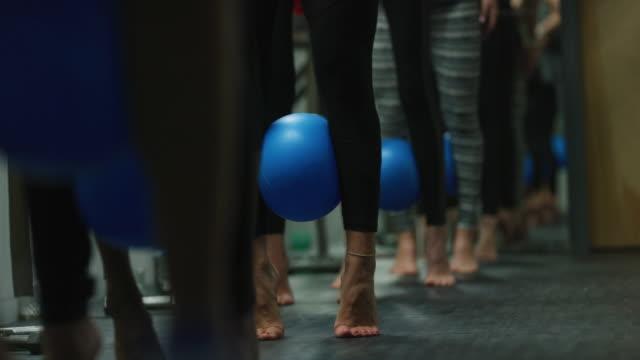 ett multietniskt gäng kvinnor puls med en fitness boll mellan sina kalvar i en klass på en motion studio - balettstång bildbanksvideor och videomaterial från bakom kulisserna