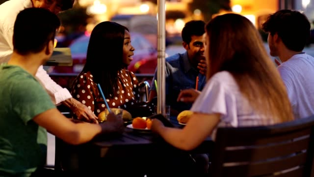 Multi-ethnic group of young adult friends at outdoor cafe. video