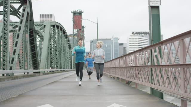 Multi-Ethnic Group Running over a Bridge video