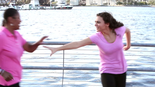 Multi-ethnic group, women in pink walking on waterfront video