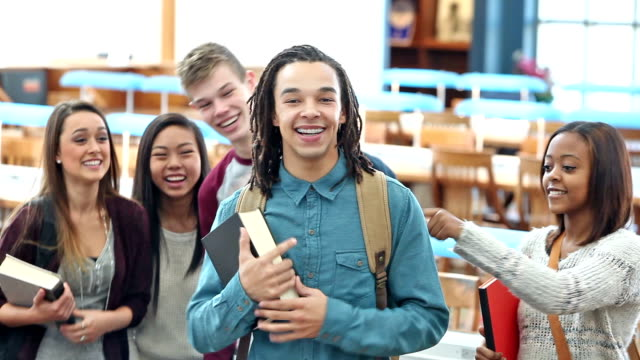 Multi-ethnic high school students in library being silly video