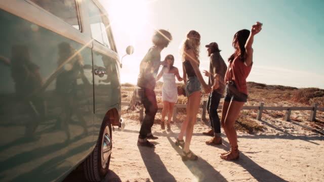 multi-etnico fricchettone gli amici ridendo e feste, balli accanto alla van - hippy video stock e b–roll