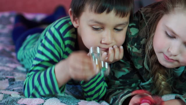 multi-ethnic Little boy and girl playing with the spinner lying on the couch 4K video