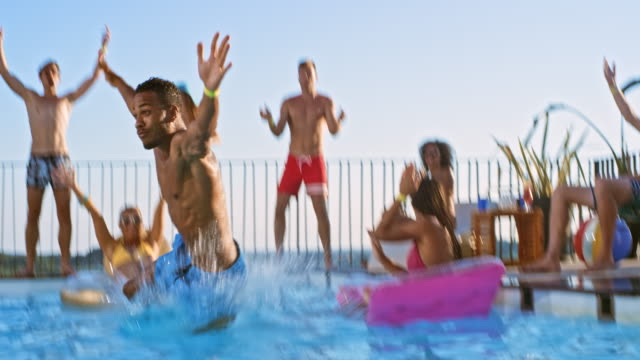SLO MO DS Multiethnic man doing a funny jump into the pool while friends are cheering for him Slow motion wide low angle dolly shot of a multiethnic man doing a funny jump into the water at a pool party while his friends are cheering for him. Shot in Slovenia. pool party stock videos & royalty-free footage
