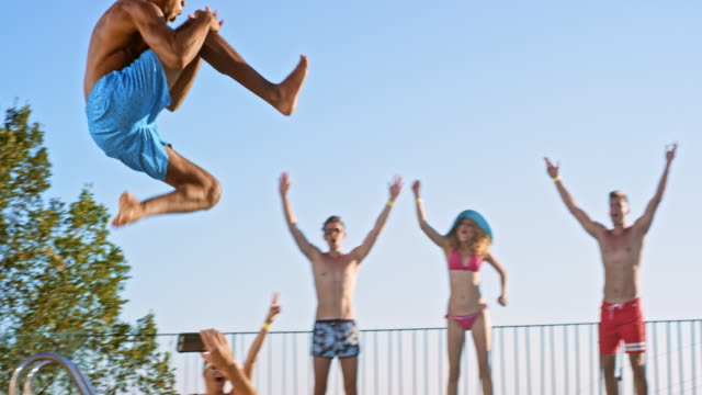 SLO MO DS Multiethnic man jumping into the pool and his friend are cheering for him Slow motion wide low angle dolly shot of a multiethnic man jumping into the pool on a hot day while his friends are cheering for him. Shot in Slovenia. pool party stock videos & royalty-free footage
