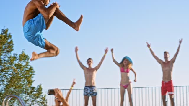 slo mo ds multietniskt man hoppa i poolen och hans vän hejar för honom - kille hoppar bildbanksvideor och videomaterial från bakom kulisserna
