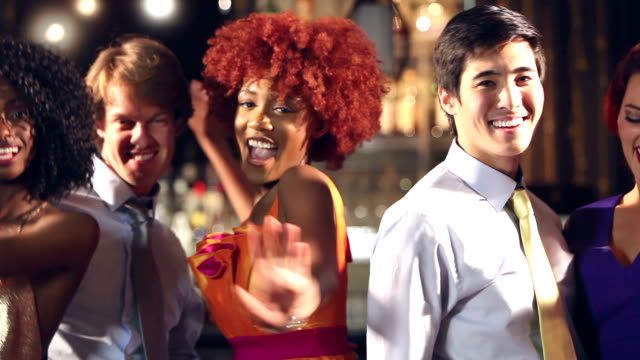 Multi-ethnic men and women dancing at bar A multi-ethnic group of young men and women in their 20s and 30s having fun dancing at a bar. They are standing in a row, smiling at the camera. the men are wearing shirts and ties, so this may be an after work party. party social event stock videos & royalty-free footage