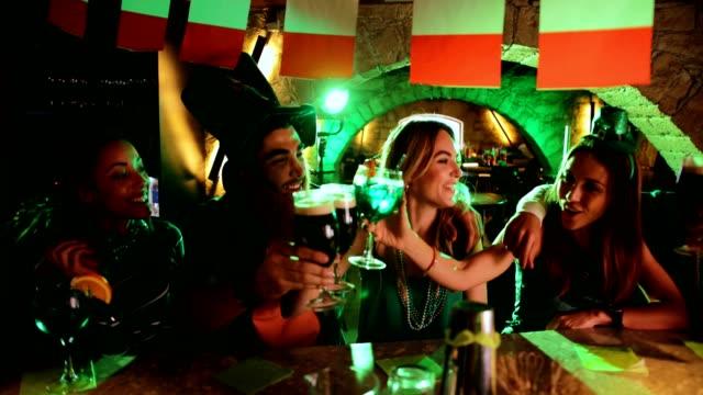 vídeos y material grabado en eventos de stock de y multiétnicos hombres y mujeres tener bebidas en el día de san patricio - día de san patricio