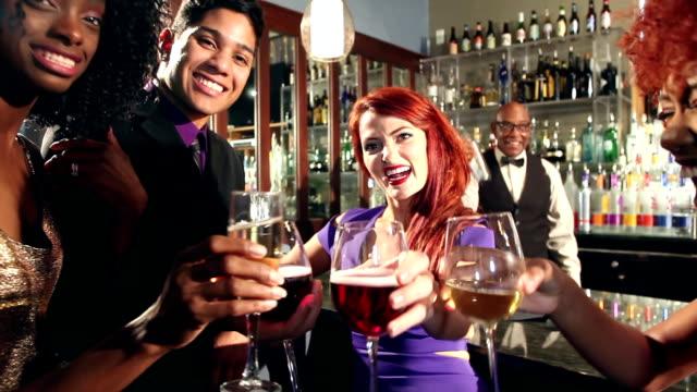 vídeos de stock, filmes e b-roll de multi-étnica homens e mulheres se divertindo bebendo no bar - festa da empresa