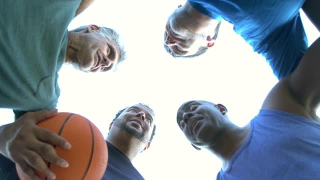stockvideo's en b-roll-footage met multi-etnische mannen spelen basketbal, praten in huddle - huddle