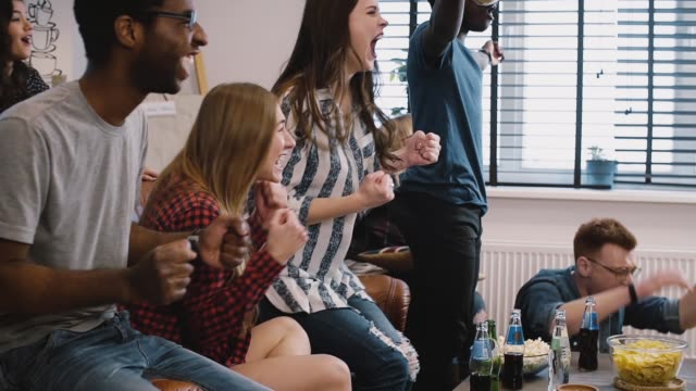 Multi-ethnic millennial fans watch sports on TV. Supporters celebrate win and success. Smiling and laughing. Emotion video