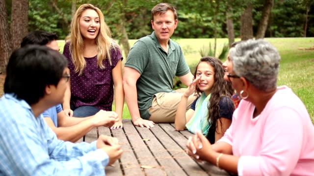 Multiétnico, mezclada edad grupo de amigos para reuniones junto al parque. - vídeo