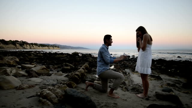 multi-ethnic romantic couple proposing at the beach - помолвка стоковые видео и кадры b-roll