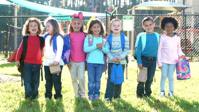 vídeos de stock e filmes b-roll de multi-ethnic school children standing in a row - mochila saco