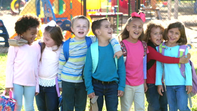 Multi-ethnic school children standing in a row A group of multi-ethnic school children with backpacks and lunch bags, standing in a row, looking at the camera, laughing and smiling. The girl with the white bow in her hair has down syndrome. elementary age stock videos & royalty-free footage