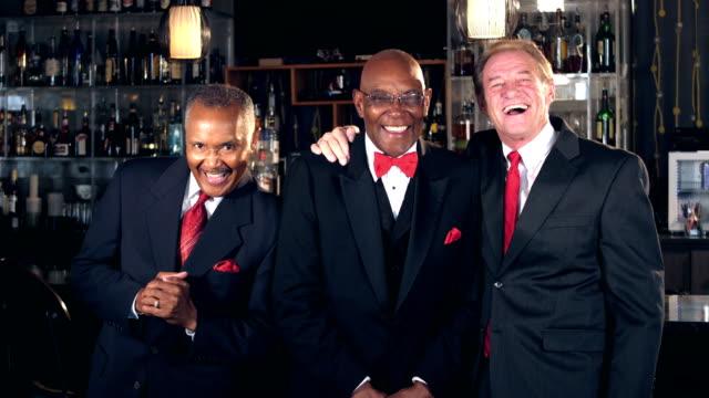 Multi-ethnic senior men at bar wearing suits, laughing video