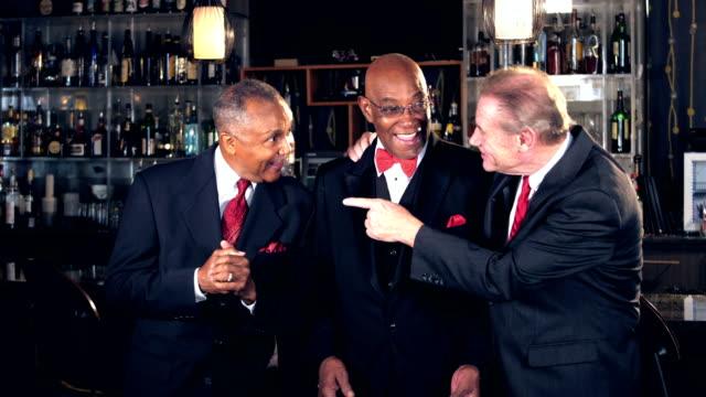 vidéos et rushes de hommes seniors multiethniques au bar portant costumes, parler - soirées habillées