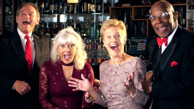 Multi-ethnic seniors at bar enjoying night out, surprise video