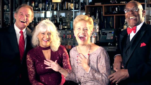 Multi-ethnic seniors at bar, laughing at camera video