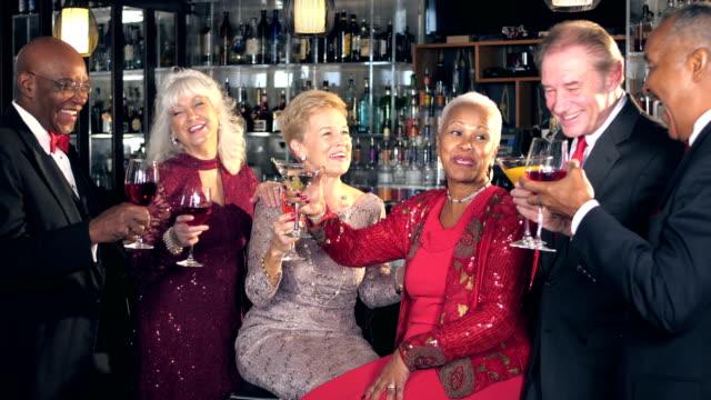 vídeos de stock, filmes e b-roll de idosos multiétnicas no bar, brindando - festa da empresa