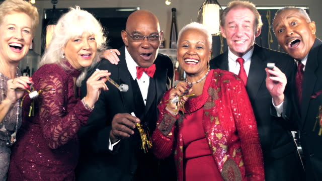 Multi-ethnic seniors celebrating with party horns video