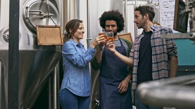 multi-etniska skickliga craft brewers firar framgången för bryggeriet company - mellan 30 och 40 bildbanksvideor och videomaterial från bakom kulisserna