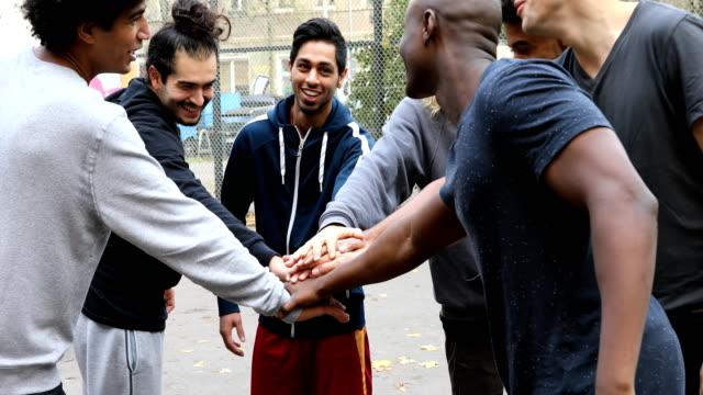 multi-ethnic soccer team stacking hands on street - tylko mężczyźni filmów i materiałów b-roll