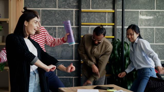 vídeos de stock, filmes e b-roll de colegas de negócios start-up multi-étnica divirta-se dançando no escritório sotão e comemorando o sucesso do projeto - festa da empresa