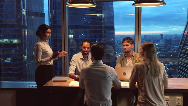 Multiethnic startup business team gathered together in modern office boardroom Multiethnic startup business team gathered in modern office boardroom, working until late, skyscrapers, night city view through panoramic window. Motivated ambitious workgroup brainstorming concept colleague stock videos & royalty-free footage