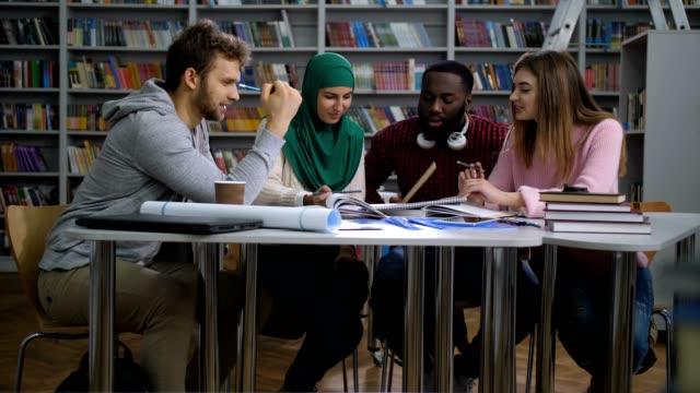 multiethnische studenten arbeiten an uni-projekt - religion stock-videos und b-roll-filmmaterial
