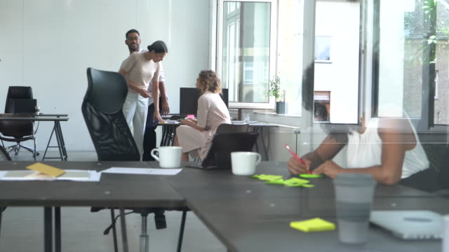 Multiethnic team at work Businesspeople working at office. On the foreground a businesswoman is working at her desk handwriting notes, while on the background a team of 3 are having an informal meeting. coworking stock videos & royalty-free footage