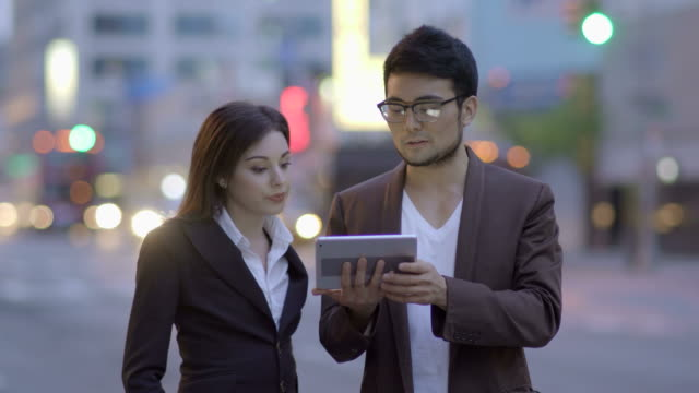 Multi-Ethnic Team of Business People Working With a Tablet. Looking at Screen and Talking Business. video