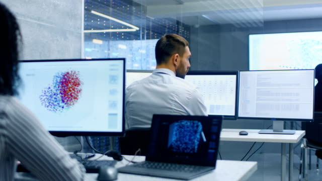 Video Multi-Ethnic Team of Computer Scientists Create Neural Network at Their Workstation. Office is Full of Displays Showing 3D Representations of Neural Networks.