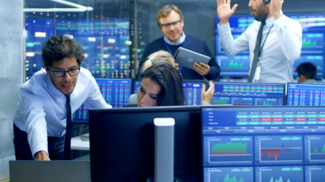 multi-ethnic team of stock traders at the stock exchange firm office is busy selling and buying bonds and shares. they made successful deal and celebrate. - stock broker stock videos & royalty-free footage