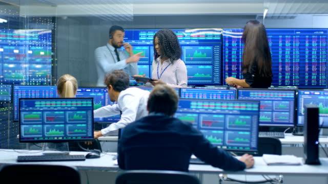トレーダーの多民族のチームでは、証券取引所のオフィスで成功日があります。ディーラーとブローカーを購入する市場で株式を売却それらの祝う収益性の高いトランザクション。モニターには、関連するインフォ グラフィック、データや数字が表示されます。 ビデオ
