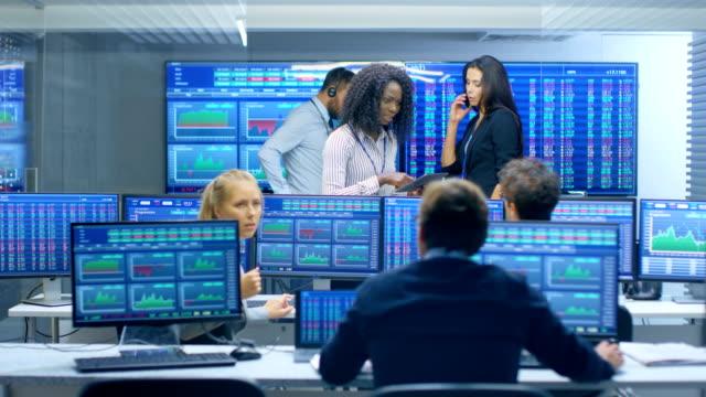 stockvideo's en b-roll-footage met multi-etnische team van handelaren is druk werken, praten en geven opdrachten aan elkaar op het kantoor van de stock exchange. dealers en makelaars kopen en verkopen voorraden op de markt. monitoren weergegeven relevante infographics, gegevens en cijfers. - lood
