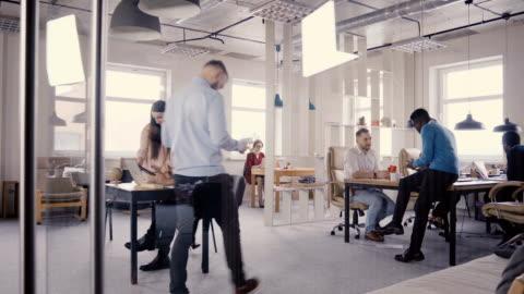 wieloetniczny zespół pracujący w nowoczesnym modnym biurze. szczęśliwi młodzi uśmiechnięci kreatywni millenialsi pracują w lekkim coworkingu 4k - relaks filmów i materiałów b-roll
