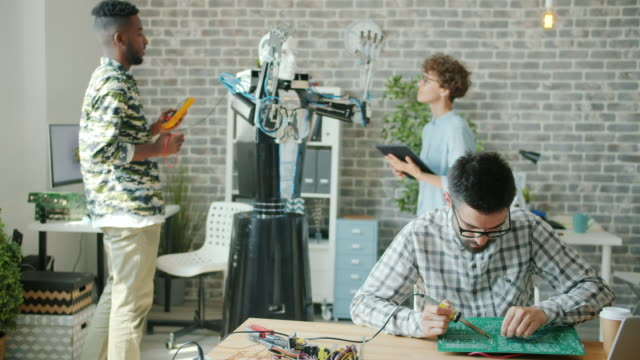 Multi-ethnic team working in office testing droid soldering circuit board