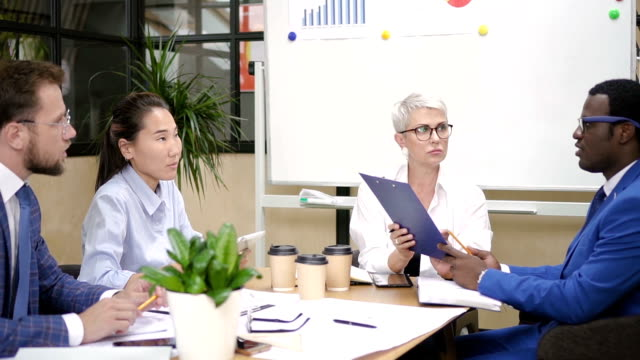Multi-ethnic team working together in office board room