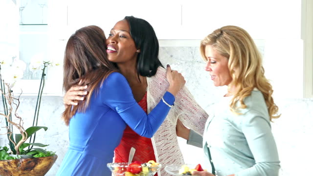 Mujeres multiétnicas en cocina saludo, abrazos - vídeo