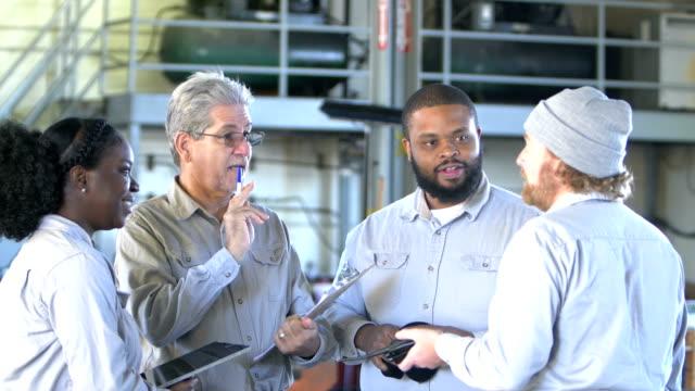 Multi-ethnic workers in repair shop having meeting