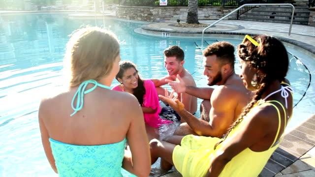 Multi-ethnic young adults having fun in swimming pool video